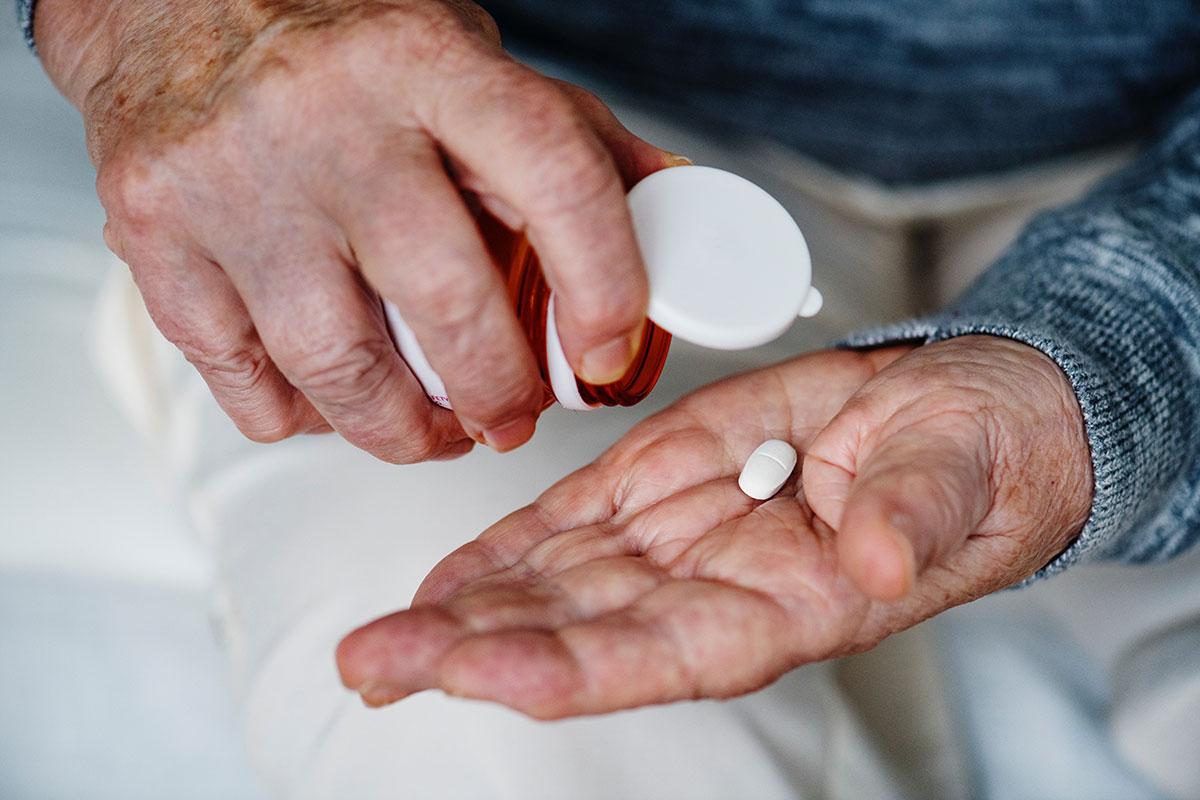 old man holding medicine tablet