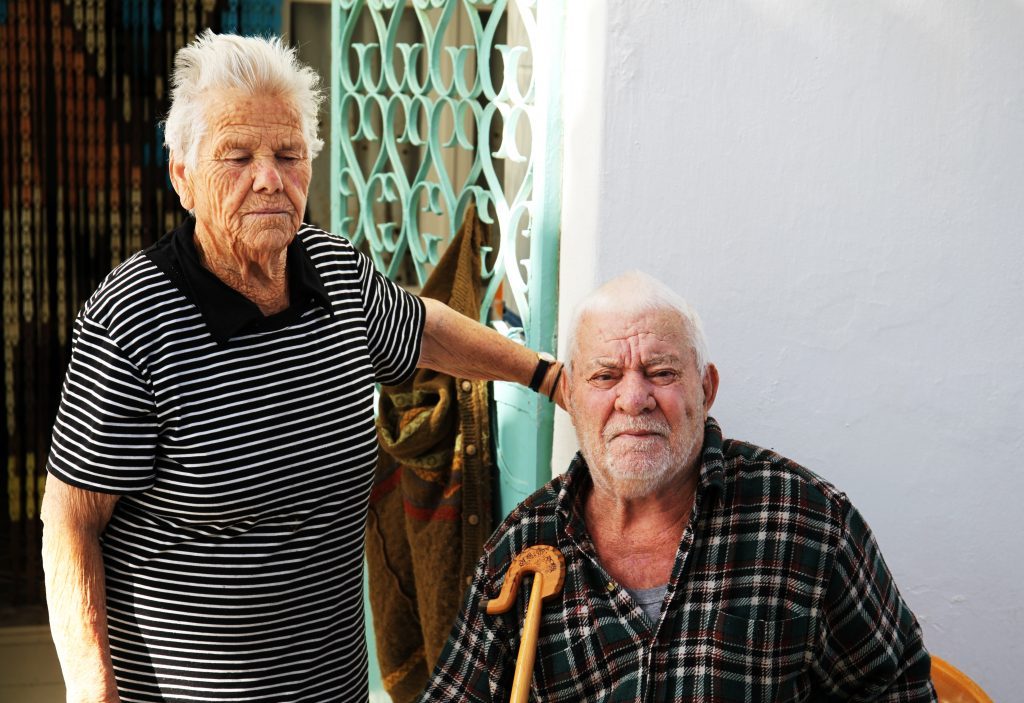 old woman standing beside a sitting old man
