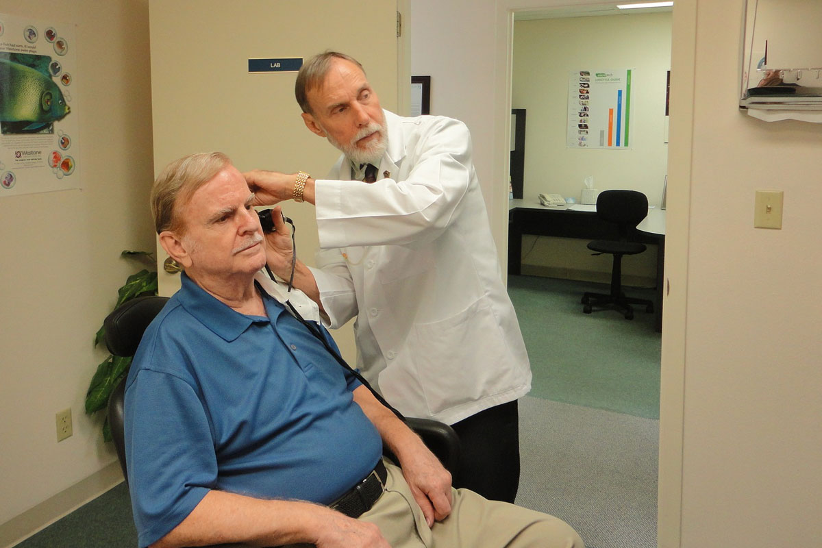 doctor checking old man's ear